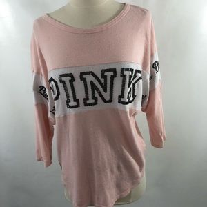 A pink and white long sleeve with black lettering